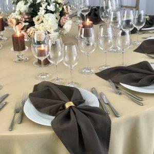 Pilkai rudos spalvos stalo servetėlė 50x50cm. Nuomos kaina 0,5 €.