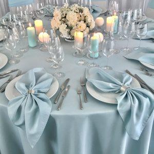 Žydros spalvos stalo servetėlė 50x50cm. Nuomos kaina 0,5 €.