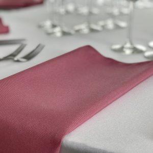 Tamsiai rožinės spalvos stalo servetėlė 50x50cm. Nuomos kaina 0,5 €.