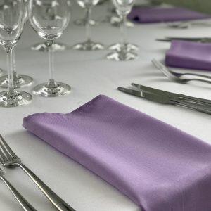 Violetinė, alyvos spalvos stalo servetėlė 50x50cm. Nuomos kaina 0,5 €.