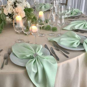 Šviesiai žalios spalvos stalo servetėlė 50x50cm. Nuomos kaina 0,5 €.