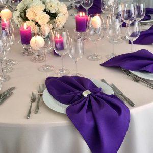 Violetinės spalvos stalo servetėlė 50x50cm. Nuomos kaina 0,5 €.