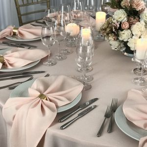 Koralų spalvos stalo servetėlė 50x50cm. Nuomos kaina 0,5 €.